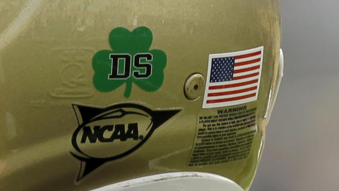 """FILE - In this Oct. 30, 2010, file photo, Notre Dame kicker Brandon Walker wears a """"DS"""" sticker honoring Declan Sullivan before the start of a NCAA college football game against Tulsa in South Bend, Ind.  Sullivan would have been in his element this weekend, video camera at hand, adding his own sly observations about the team for which he grew up rooting and served as a film assistant until his tragic death in October 2010.  (AP Photo/Michael Conroy, File)"""