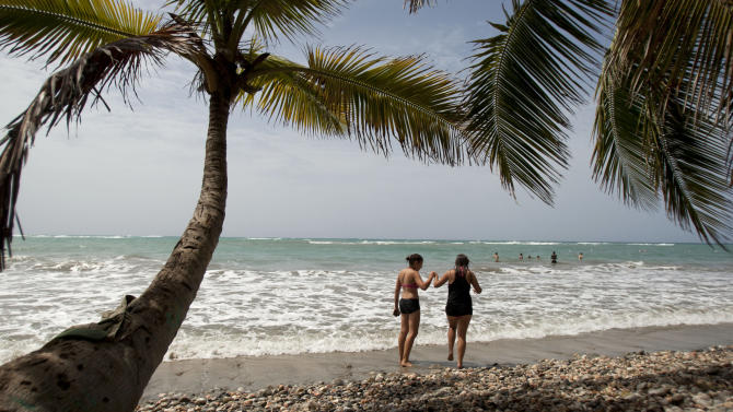 In this June 28, 2013 photo, tourists walk on the shore of the Raymond les bains beach in Jacmel, Haiti. The Haitian government is to trying to revive the country's long stagnant tourism industry with investments totaling more than $160 million. While many in Haiti welcome anything that can create jobs, some critics are questioning the government's priority of trying to attract high-end tourists at a time when the country faces so many other problems, such as high unemployment, a deadly cholera outbreak and lack of housing for people displaced by the earthquake more than three years ago. (AP Photo/Dieu Nalio Chery)