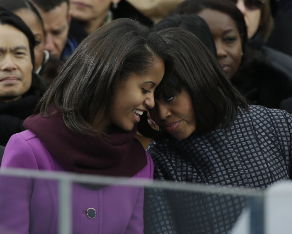 First lady Michelle Obama speaks with her daughter Sasha at the ceremonial swearing-in for President Barack Obama at the U.S. Capitol during the 57th Presidential Inauguration in Washington, Monday, Jan. 21, 2013. (AP Photo/Pablo Martinez Monsivais)