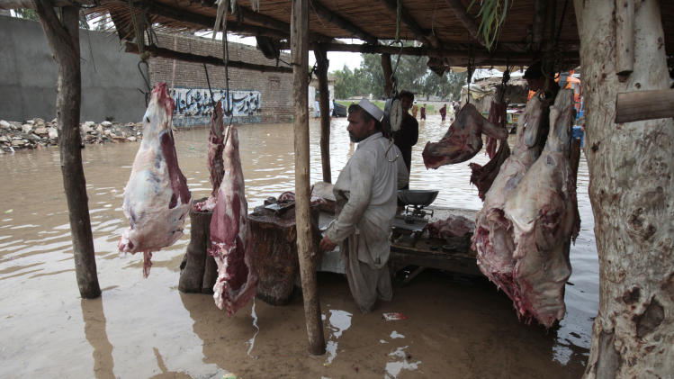 A Pakistani butcher waits for customers at a flooded street in Nowshera, near Peshawar, Pakistan on Wednesday, Aug. 22, 2012. Local meteorologists fear heavy rains fall may cause flooding in some areas of northwest Pakistan. (AP Photo/Mohammad Sajjad)