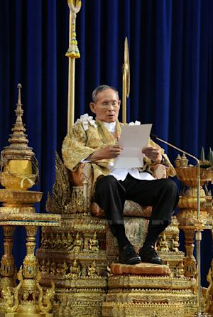 In this photo released by Thailand's Royal Household Bureau, Thailand's King Bhumibol Adulyadej reads a statement at Klai Kangwon Palace during a ceremony in celebration of his 86th birthday in Prachuap Khiri Khan province, Thailand, Thursday, Dec. 5, 2013. Thailand put politics aside Thursday to celebrate the birthday of the country's revered monarch, who used his annual birthday speech to call for stability but made no direct reference to the crisis that has deeply divided the nation. (AP Photo/Royal Household Bureau)