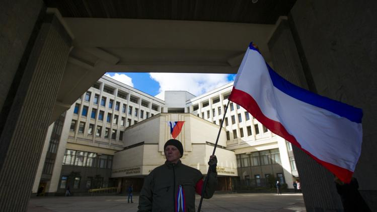 A man holding a Crimean flag stands guard outside the local parliament in the Crimean capital of Simferopol