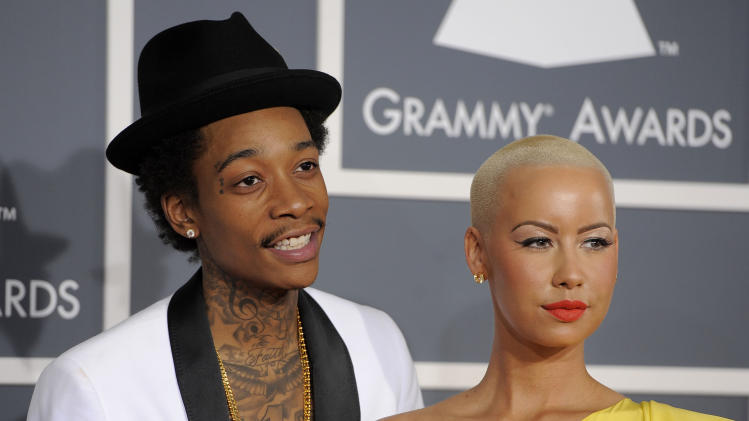 "FILE - This Feb. 12, 2012 file photo shows Wiz Khalifa, left, and Amber Rose at the 54th annual Grammy Awards in Los Angeles. Khalifa says the preparation of becoming a first-time father and husband has helped put him in a more mature musical state of mind. ""I'm at a different point of my life,"" said Khalifa, whose sophomore album, ""O.N.I.F.C.,"" debuted at No. 2 on Billboard's 200 albums chart Wednesday with more than 141,000 copies sold, according to Nielsen Scan. (AP Photo/Chris Pizzello, file)"