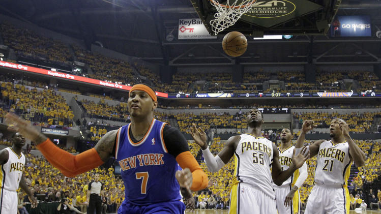 New York Knicks' Carmelo Anthony (7) reacts in front of Indiana Pacers' Roy Hibbert (55), Paul George and David West (21) during the first half of Game 6 of an Eastern Conference semifinal NBA basketball playoff series Saturday, May 18, 2013, in Indianapolis. (AP Photo/Darron Cummings)