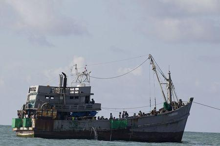 A boat packed with migrants is attached to a Myanmar navy vessel off Leik Island in the Andaman sea