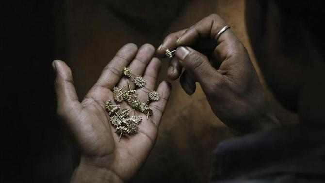 A worker examines gold earrings inside a gold jewellery factory in New Delhi August 13, 2013. REUTERS/Anindito Mukherjee/Files