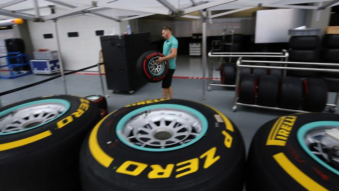 A Mercedes Formula One crew member arranges tyres in the team's garage ahead of the Singapore F1 Grand Prix at the Marina Bay street circuit in Singapore