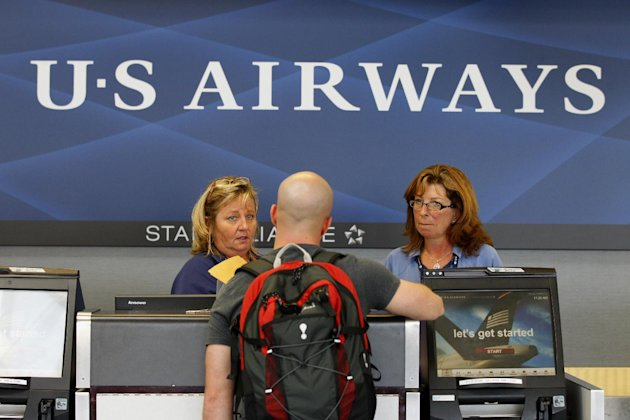 In this Thursday, Sept. 27, 2012, photo, US Airways employees assist a customer at a ticket counter at the Charlotte/Douglas International airport in Charlotte, N.C. US Airways made its best profit ever for the 3-month stretch that covers much of the peak summer vacation season. Net income for the third quarter totaled $245 million, or $1.24 per share, compared with $76 million, or 41 cents per share, a year earlier, the airline said Wednesday, Oct. 24, 2012. (AP Photo/Chuck Burton)