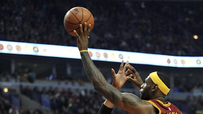 Cleveland Cavaliers' LeBron James (23) goes up for a shot against Chicago Bulls' Taj Gibson (22) during the first half of an NBA basketball game in Chicago, Friday, Oct. 31, 2014. (AP Photo/Paul Beaty)