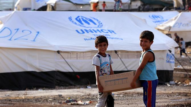 Young Iraqis who fled violence carry a parcel of food at the Bahrka camp on August 20, 2014
