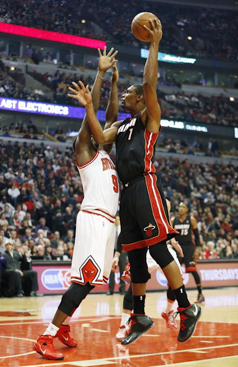 Miami Heat center Chris Bosh, right, shoots over Chicago Bulls forward Luol Deng, left, during the first half of an NBA basketball game in Chicago, Thursday, Dec. 5, 2013