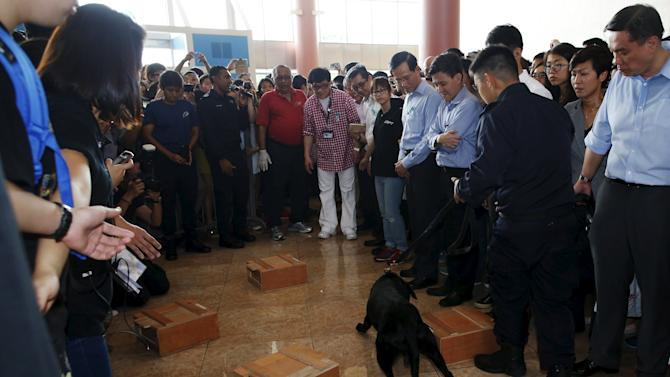 Singapore's new anti-drug ambassador Jackie Chan watches a demonstration by drug sniffing dogs after launching an anti-drug mobile game application at Nanyang Polytechnic in Singapore