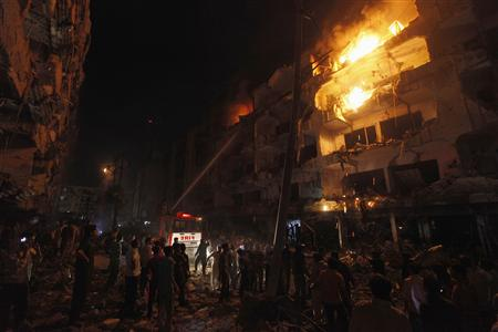 Firefighters spray water to control a fire in a building after a bomb blast in a residential area in Karachi