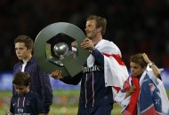 Paris Saint-Germain&#39;s David Beckham raises the French Championship trophy at the end of their team&#39;s French Ligue 1 soccer match against Brest at the Parc des Princes stadium in Paris May 18, 2013. His sons Brooklyn (back L), 14, Romeo (R), 10, and Cruz, 8, stand beside him.      REUTERS/Gonzalo Fuentes (FRANCE  - Tags: SPORT SOCCER)