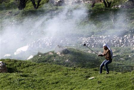 A Palestinian protester uses a sling shot to throw a stone at Israeli soldiers and border policemen during clashes at Hawara checkpoint near the West Bank city of Nablus February 24, 2013. REUTERS/Abed Omar Qusini