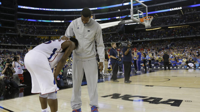 Kansas' Elijah Johnson is consoled after losing 87-85 to Michigan in overtime of a regional semifinal game in the NCAA college basketball tournament, Friday, March 29, 2013, in Arlington, Texas. (AP Photo/Tony Gutierrez)