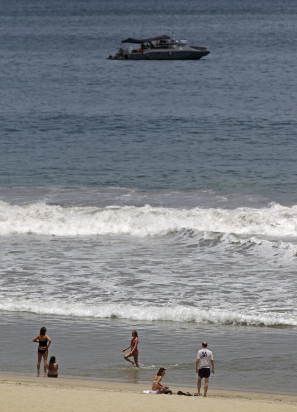 Tourists enjoy the beach of San Jose del Cabo in Mexico's Baja California Peninsula as a Mexican Navy boat patrol on Sunday, June 17, 2012. The G-20 summit starts in Los Cabos on Monday. (AP Photo/Eduardo Verdugo)