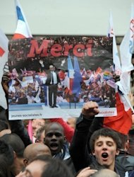 A supporter of Socialist Party (PS) newly elected French President holds a party poster on May 6, 2012 outside the party's headquarters following the announcement of the estimated results of the second round of Presidential election