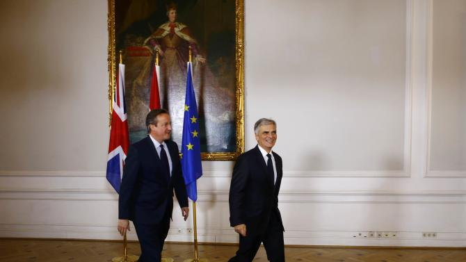 Austria's Chancellor Faymann and Britain's Prime Minister Cameron walk in front of a painting of former Austrian Empress Maria Theresia in the chancellery in Vienna