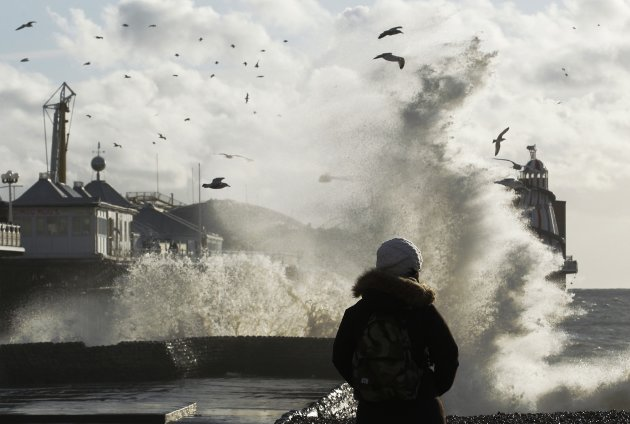 A woman watches giant waves …