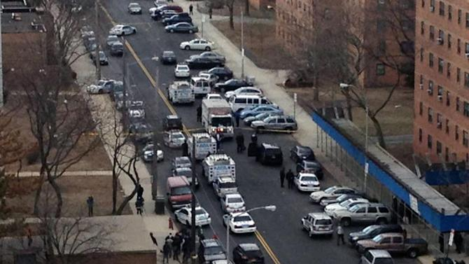 This photo provided by News 12, shows the scene near the Gravesend Houses in Coney Island, New York on Friday, March 22, 2013, after a shooting took place near a public housing project. Police said Friday there are three male victims and one female victim. One of the men was killed. (AP Photo/News 12) MANDATORY CREDIT
