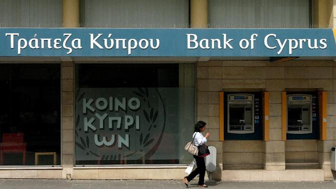 """A woman passes outside a branch of Bank of Cyprus in the main shopping street in central capital Nicosia, Cyprus, Sunday, April 14, 2013. Cyprus' President Nicos Anastasiades has chided the central bank chief to not act in ways that """"catch the government by surprise,"""" but to move to stabilize the country's troubled banking sector. (AP Photo/Petros Karadjias)"""