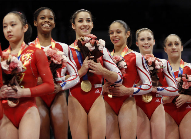 USA'S gymnasts from second left, Gabrielle Douglas, Alexandra Raisman, Sabrina Vega, McKayla Maroney and Jordyn Wieber, celebrate on the podium after winning the women's team final at  the Artistic Gy