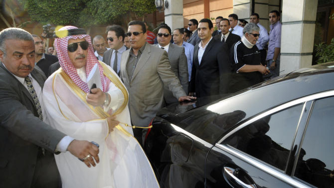 Ahmed Kattan, Saudi Arabia's ambassador to Egypt, is guided to a waiting car after his arrival in Cairo, Egypt, Saturday, May 5, 2012. Saudi Arabia's ambassador has returned to Cairo a week after he was recalled following a wave of protests against the detention of an Egyptian lawyer, the embassy said Saturday. (AP Photo/Ahmed Hammad)