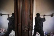 In this Wednesday, Dec. 5, 2012 photo, a Free Syrian Army fighter uses a tool to break a hole in the wall of a residents' home during heavy clashes with government forces in Aleppo, Syria. (AP Photo/Narciso Contreras)