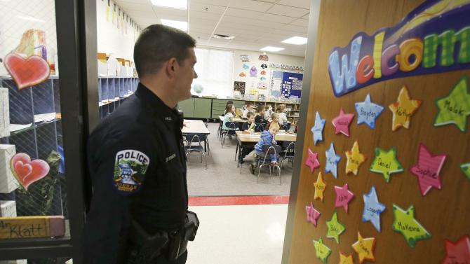 In a photo made Thursday, Feb. 21, 2013, police officer Jeff Strack looks into a classroom at Jordan Elementary School in Jordan, Minn. In what is believed to be the first of its kind nationwide, the small city south of Minneapolis is taking school security to a new level by  setting up satellite offices inside the public school buildings. (AP Photo/Jim Mone) (AP Photo/Jim Mone)