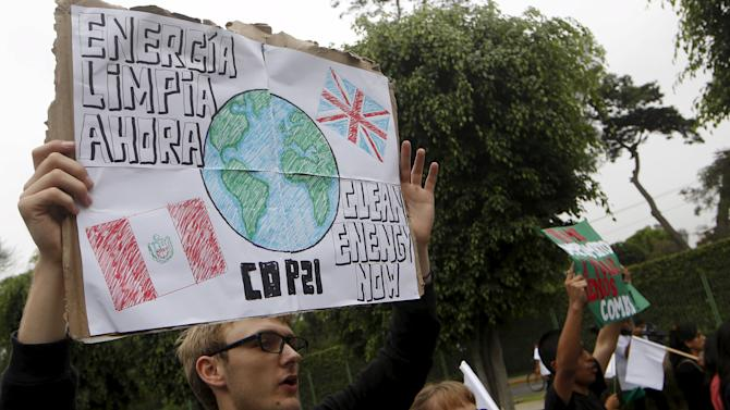 Protester holding a banner takes part in a rally ahead of the 2015 Paris Climate Change Conference (COP21), in Lima, Peru