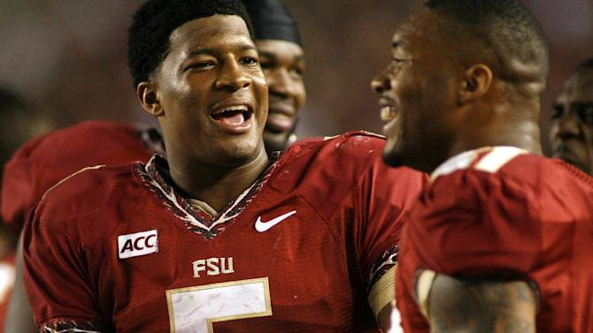 Florida State quarterback Jameis Winston (5) chats with defensive end Chris Casher (21) on the sidelines in the third quarter of an NCAA college football game against Syracuse on Saturday, Nov. 16, 2013 in Tallahassee, Fla. Florida State beat Syracuse 59-3
