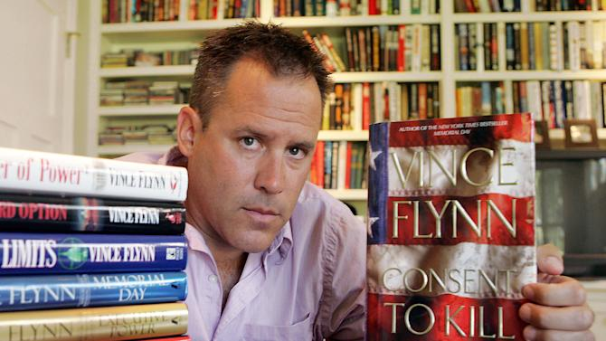"""FILE - In a Sept. 2, 2005 file photo, best-selling author Vince Flynn poses with the dust jacket of his new book, """"Consent to Kill,"""" and copies of his six other books in his home in Edina, Minn. Flynn died, Wednesday, June 18, 2013, after a two-year battle with prostate cancer, a statement from Flynn's publisher, Simon & Schuster, Inc., said. He was 47. (AP Photo/Jim Mone, File)"""