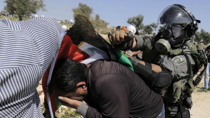 Israeli border policeman uses pepper spray to detain a Palestinian protester during clashes at a weekly demonstration against Jewish settlements in the West Bank village of Bilin, near Ramallah