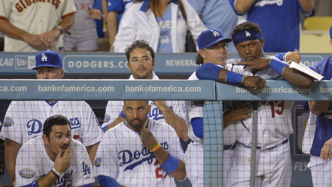 Members of the Los Angeles Dodgers watch from the dugout during the ninth inning of their baseball game against the San Francisco Giants, Tuesday, Oct. 2, 2012, in Los Angeles. The Giants won the game 4-3. With that loss, the Dodgers were eliminated from playoff contention. (AP Photo/Mark J. Terrill)
