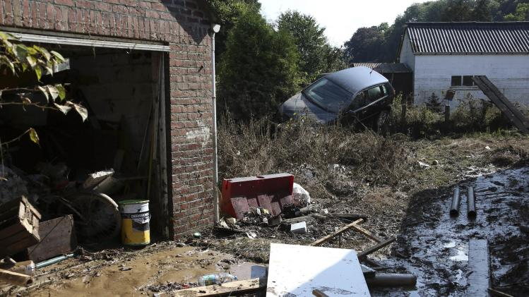 A car is seen stranded in a garden after heavy rains and floods hit the town of Ittre