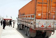Pakistani soldiers check the documents of a first container truck carrying NATO supplies prior to crossing the border into Afghanistan at the border town of Chaman