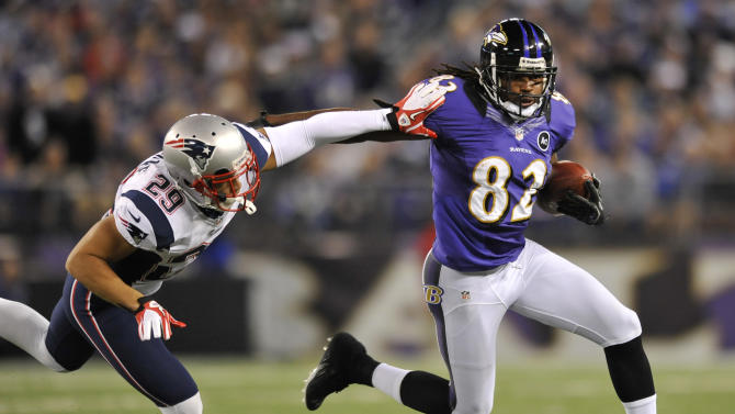 Baltimore Ravens wide receiver Torrey Smith, right, rushes the ball past New England Patriots safety Sterling Moore in the second half of an NFL football game in Baltimore, Sunday, Sept. 23, 2012. (AP Photo/Gail Burton)