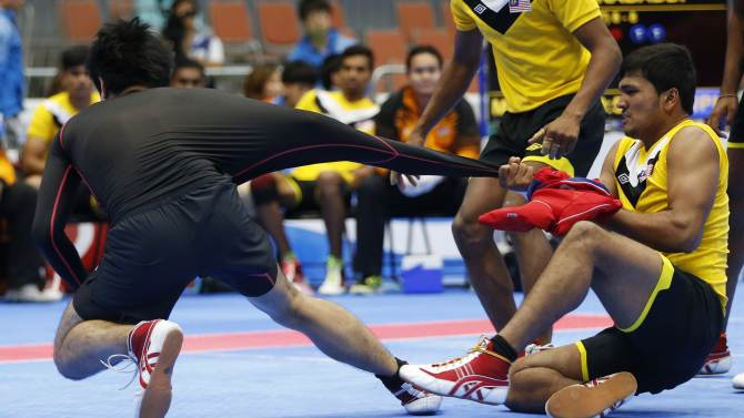Malaysia's Justin Johnson pulls Japan's Kazuhiro Takano's sleeve during their men's kabaddi match at the Songdo Global University Gymnasium during the 17th Asian Games in Incheon