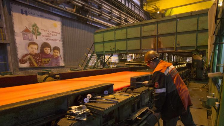 A steelworker makes measurements of a steel billet at the Ilich iron and steel plant in the southern coastal town of Mariupol