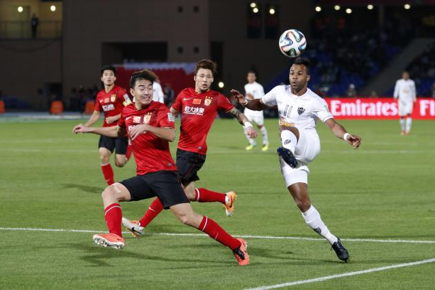Fernandinho of Brazil's Atletico Mineiro fights for the ball with Zhang Linpeng of China's Guangzhou Evergrande during their 2013 FIFA Club World Cup third place soccer match at Marrakech stad