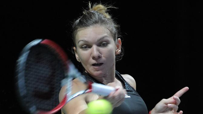 Simona Halep from Romania returns a shot to Serena Williams of the US during the WTA finals in Singapore on October 22, 2014