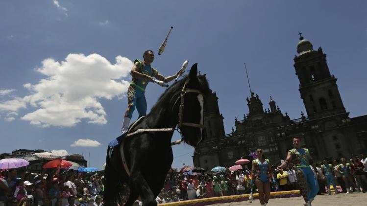 A circus worker performs atop a horse as part of a protest against a law prohibiting the use of animals in circuses, in Mexico City
