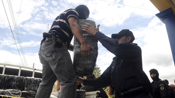 Honduras national policemen unload packages of cocaine that were brought to Tegucigalpa, Honduras, Tuesday July 3, 2012. The cocaine was seized from a small airplane that crashed after it was being chased by military planes and helicopters of the Honduras army near the town of Los Lirios, about 217 miles (350 km) east of Tegucigalpa. One of the pilots died and the other was injured. About 1322 lbs. (600 kg.) of cocaine were seized. (AP Photo/Fernando Antonio)