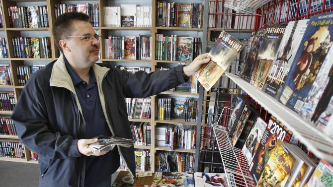 Ron Bufalini, from Ambridge, Pa., looks over the free comic books available at the New Dimensions Comics store on Free Comic Book Day, Saturday, May 7, 2011 in Cranberry, Pa. Bufalini says he likes to take advantage of the annual give away to look into different genres of comic books as well as get a few of his favorites. (AP Photo/Keith Srakocic)