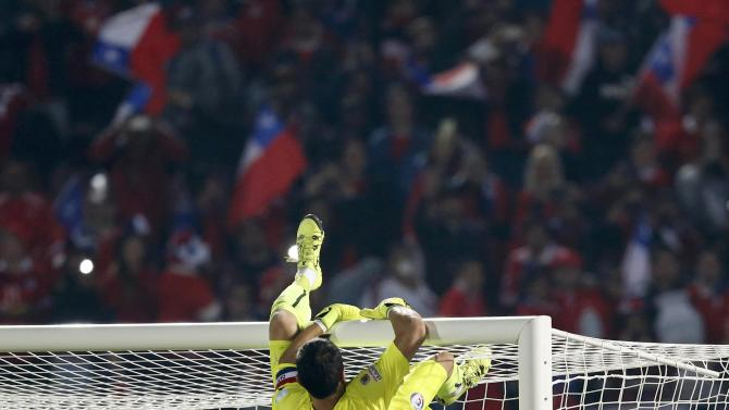 Chile's goalie Claudio Bravo climbs onto the goal after defeating Argentina to wint the Copa America 2015 at the National Stadium in Santiago
