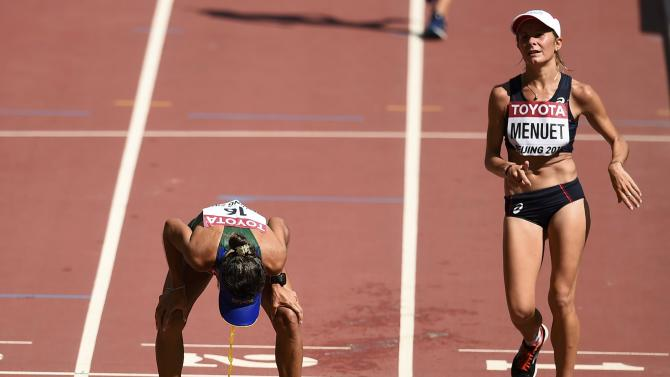 Cisiane Lopes of Brazil (L) vomits after competing in the women's 20 km race walk final during the 15th IAAF World Championships at the National Stadium in Beijing,