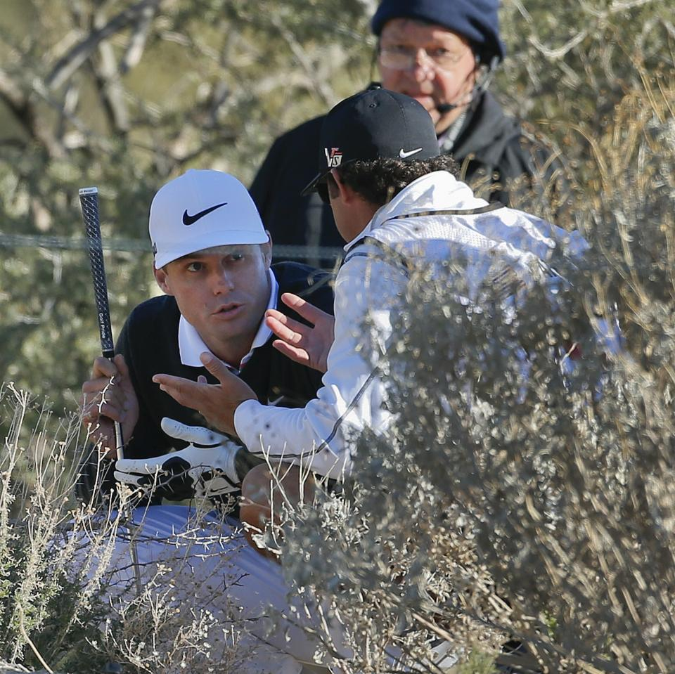 Nick Watney, left, talks to an official about hitting out of the brush in the second round of play against Steve Stricker during the Match Play Championship golf tournament, Friday, Feb. 22, 2013, in Marana, Ariz. Stricker won 1 up in 21 holes. (AP Photo/Ross D. Franklin)