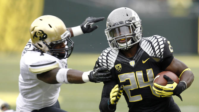 Oregon running back Kenjon Barner, right, rushes down the sideline ahead of Colorado defender Derrick Webb during the first half of an NCAA college football game in Eugene, Ore., Saturday, Oct. 27, 2012. (AP Photo/Don Ryan)