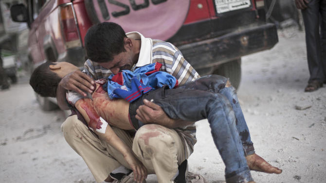 FILE - A Syrian man cries while holding the body of his son, killed by the Syrian Army, near Dar El Shifa hospital in Aleppo, Syria, Wednesday, Oct. 3, 2012. (AP Photo/Manu Brabo, File)